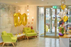 UCEM's reception area with regular balloons on the front desk and centenary balloons on the sitting area shaped as a '100'