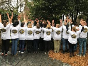 Staff members altogether raising their hands for a picture Staff members in the Purley Park garden