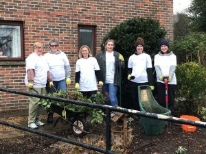 Staff members holding gardening equipment in the Purley Park garden