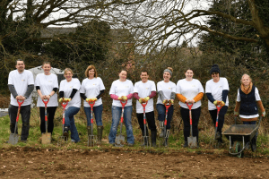 Group of staff leaning on garden forks