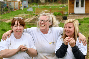 Staff members laughing whilst digging