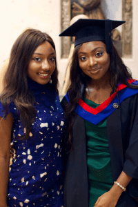 A graduate smiles for the camera with a friend in tow at the December 2019 Graduation