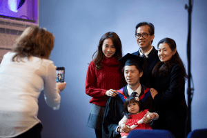 A graduate poses for a photo with his family at the December 2019 Graduation